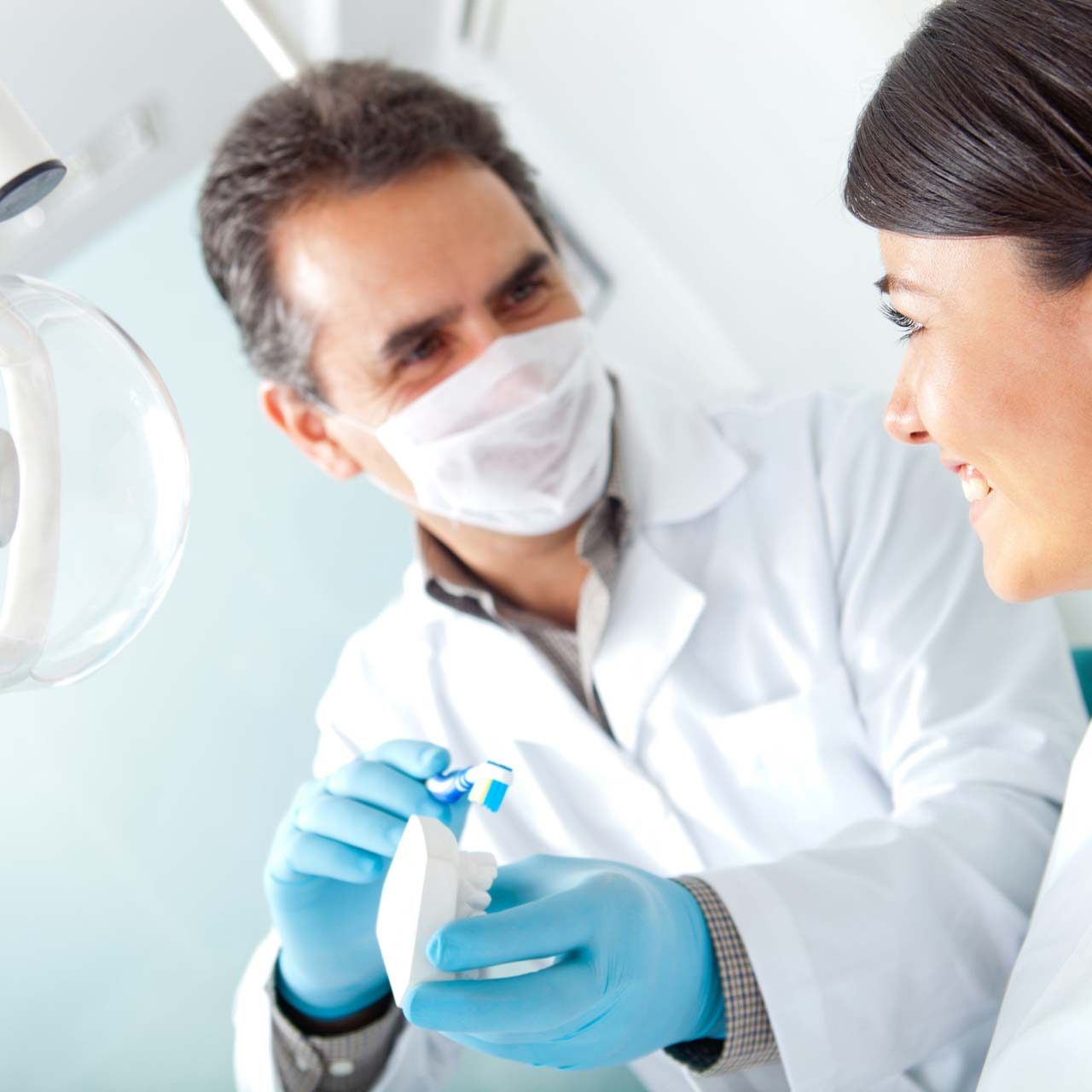 dentist_maledentistwithtoothbrushtalkingtopatient-5616x3744